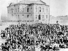 A vintage photo of a large crowd of people  Description automatically generated